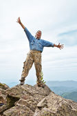 Happy mature the man costs at top of mountain, — Stock Photo