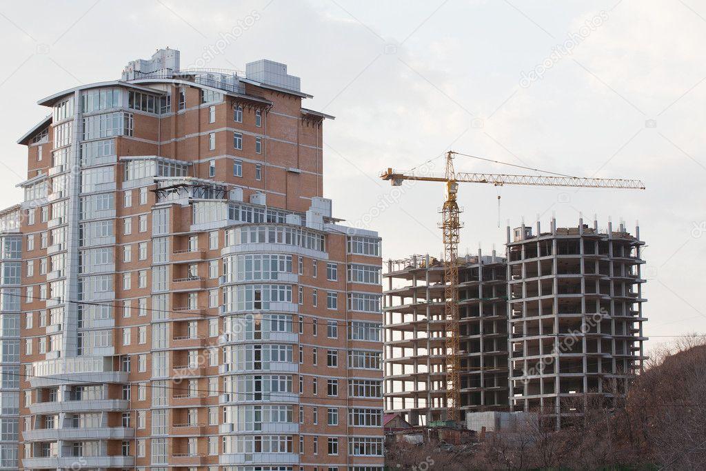 Bygga upplyftande kranen på en bakgrund av en under konstruktion flera våningar hus