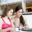Two girls work on a laptop, sitting in cafe in shopping center — Stockfoto