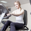 Girl in a sports hall on a velosimulator — Stock Photo