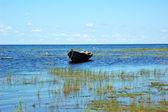 Wooden boat near the lake bank — Stock Photo