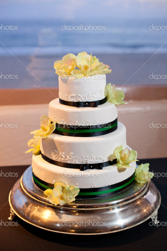 White wedding cake with black ribbon on the table at reception — Stock Photo #9776654