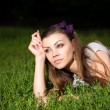 Portrait of a beautiful young woman lying on the grass — Stock fotografie