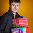 Present gifts holding man looking camera — Stock Photo #8986849