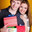 Young couple with gifts on yellow — Stock Photo #8986861