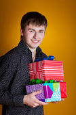 Present gifts holding man looking camera — Stock Photo