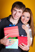 Young couple with gifts on yellow — Stock Photo