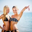 Two women on the beach showing the way — Stock Photo