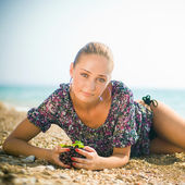 Smiling woman with grapes in the beach — Stock Photo