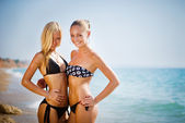 Two women on the beach smiling — Stock Photo