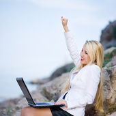 Beautiful woman on the seashore with a laptop — Stock Photo