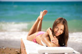 Beautiful woman on a beach on a chaise lounge — Stock Photo