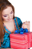Portrait of a beautiful woman opening a gift — Stock Photo