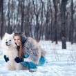 Happy woman with Samoyed dog in winter forest - Stock Photo
