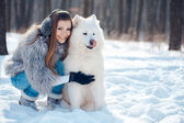 Happy woman with Samoyed dog in winter forest — Stock Photo