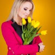 Young blond woman with flowers in her hands — Stock Photo