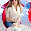 Royalty-Free Stock Photo: Pretty young woman sitting in the cafe with a cup of tea