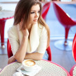 Pretty young woman sitting in the cafe with a cup of tea — Stock Photo
