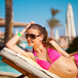 Beautiful woman on a tropical beach on a chaise lounge — Stock Photo