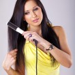Portrait of beautiful woman, she using hair straighteners — Stock Photo