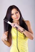 Portrait of beautiful woman, she using hair straighteners — Stock Photo
