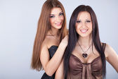 Two young beautiful women on grey — Stock Photo
