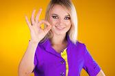 Happy smiling beautiful young woman showing okay on yellow — Stock Photo