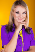 Portrait of a happy smiling beautiful young woman on yellow — Stock Photo