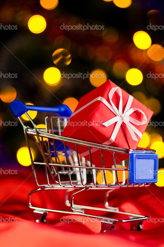 Shopping cart with decorative gift box against blurred lights on christmas tree — Stock Photo #10569159