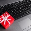 Gift on a laptop keyboard - Zdjęcie stockowe