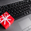 Gift on a laptop keyboard - Stock Photo