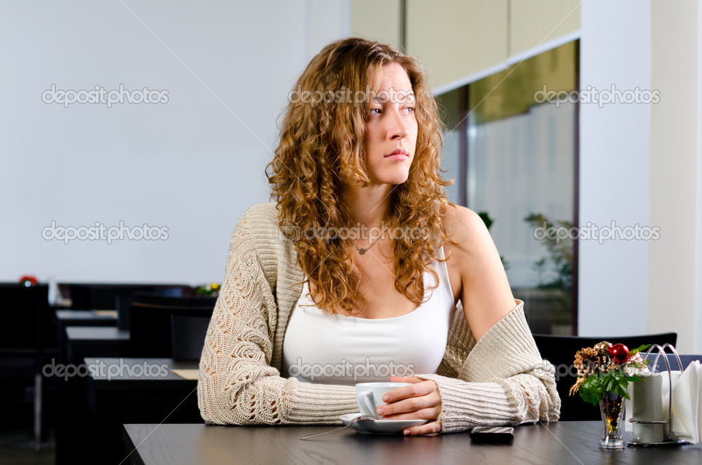 Young woman is sitting at cafe and looking sideways  Stock Photo #8081370