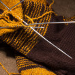 Stockfoto: Woollen scarf with knitting needles.