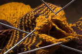 Woollen scarf with knitting needles. — Stockfoto