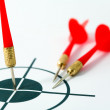 Red darts and target - Stock Photo