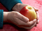Old hands with an apple — Stock Photo