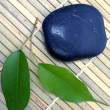 Green leaves and stones on bamboo mat — Stock Photo
