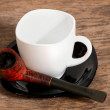 Pipe and white cup — Stock Photo