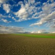 Plowed field and cloudy sky - Stock Photo