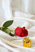 Rose and jewelry on bed — Stock Photo