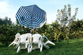 White table and chairs in a garden — Stock Photo