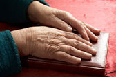 Old hands on the bible — Stock Photo