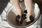 Feet in wash-basin with stones — Stock Photo