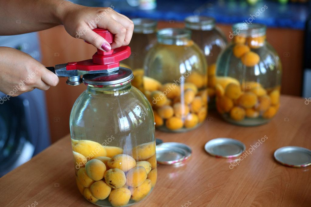 An image of hands canning a big jar of apricots — Stock Photo #8571222