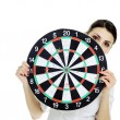 Girl holding dartboard — Stock Photo