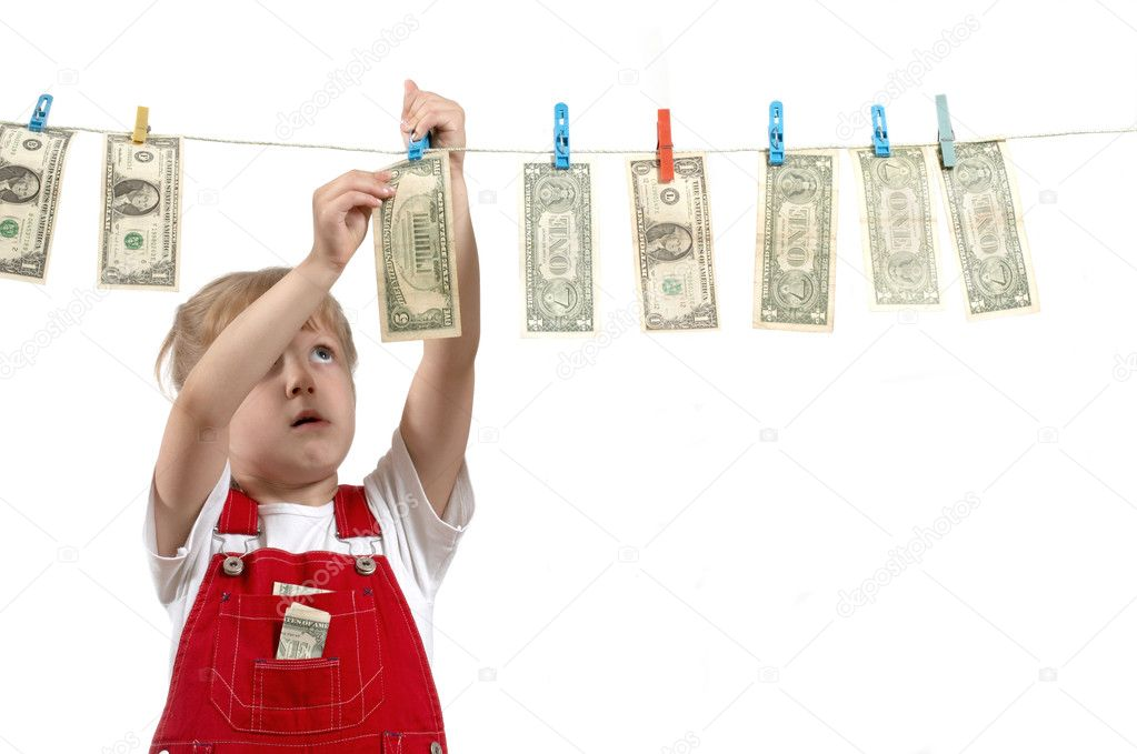 A girl in red overalls hanging up dollars — Stock Photo #8659463