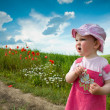 Baby-girl on a lane amongst a field — Stock Photo