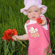Child with red flower amongst green grass - Stock Photo
