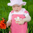 Child with red flower amongst green grass — Stock fotografie
