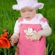 dziecko z czerwonym kwiatem wśród zieleni trawy — Zdjęcie stockowe
